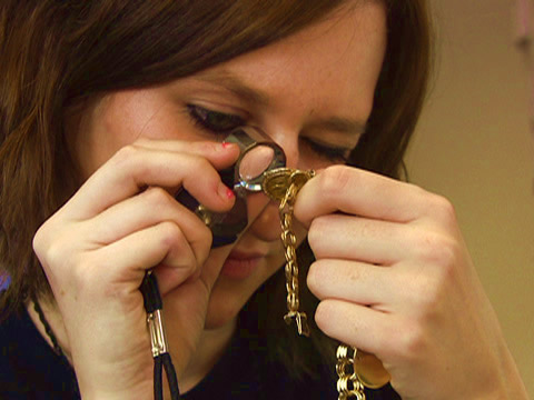 Examining gold jewellery with loupe